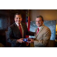 Congressman Buddy Carter presents outgoing GPA Executive Director Curtis Foltz (left) with a U.S. flag that has flown over the capitol in Washington D.C. Carter recognized Foltz' service to the state of Georgia during his final board meeting before stepping down June 30. (Photo: Georgia Ports Authority)