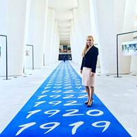 Eleni Antoniadou on ILO's 'blue carpet' with dates going back to the establishment of the organization (Photo: ILO)