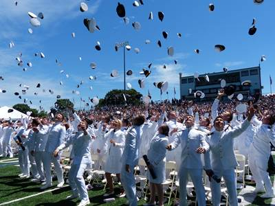Graduates from USMMA celebrate graduation by tossing covers into the air. The class of 2014 from USMMA included 225 new Merchant Marine and Military Officers. (U.S. Navy photo)