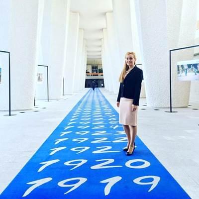 Eleni Antoniadou on ILO's 'blue carpet' with dates going back to the establishment of the organization (Photo: ILO)